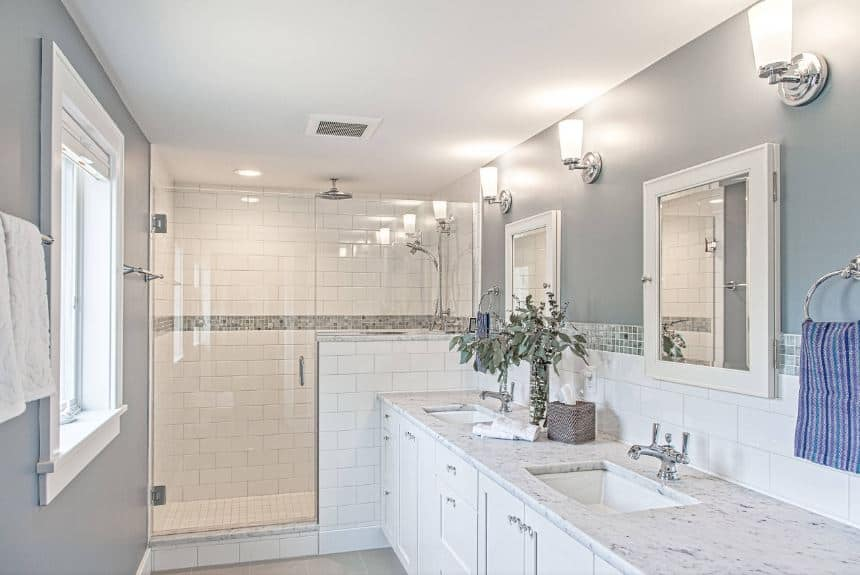 The glass-enclosed shower area on the far wall has white tiles arranged in a brick wall pattern that matches with the white vanity that houses two sinks against gray walls adorned with mirror-faced medicine cabinets topped with wall-lamps.