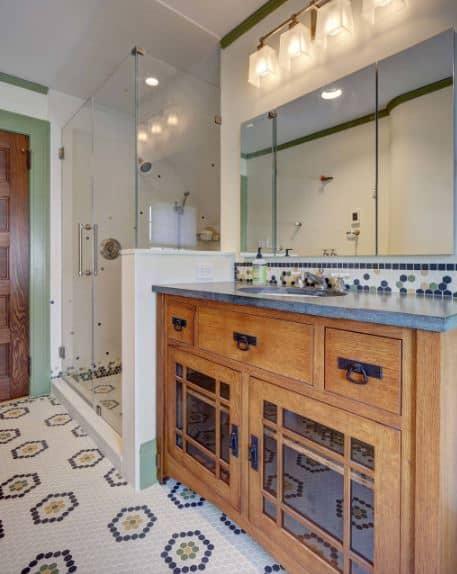 The wooden vanity has three drawers on the upper level beneath the gray countertop. The lower part of it has a pair of mirrored cabinets with an elegant and classic design that complements the colorful patterned flooring tiles.