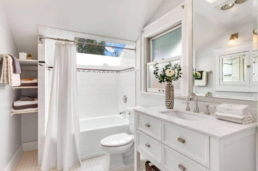 The white wooden vanity that blends with the white toilet and white bathtub has four drawers and a shelf beneath. The bathtub and shower area has a white shower curtain and a brilliant skylight above it.