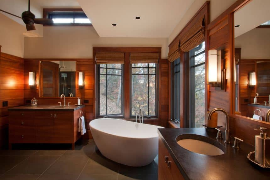 The white freestanding bathtub stand out against the rest of the bathroom that is dominated by the redwood elements on the window frames and walls that blends with the two wooden vanities illuminated by modern wall-mounted lamps.