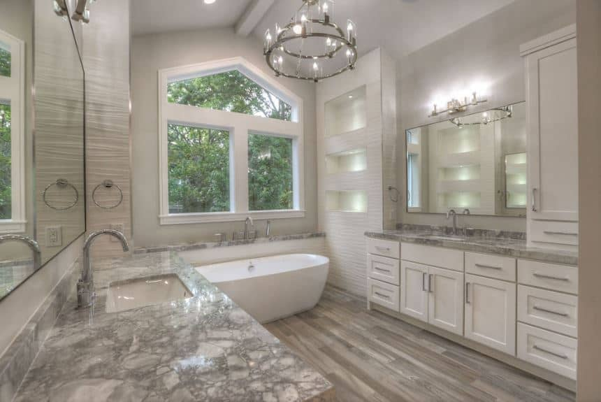 The light gray cathedral ceiling has a single exposed beam running in the middle that supports the brilliant two-tier farmhouse-style chandelier matching the wall lamp above the mirror of the vanity that has white shaker cabinets and drawers.