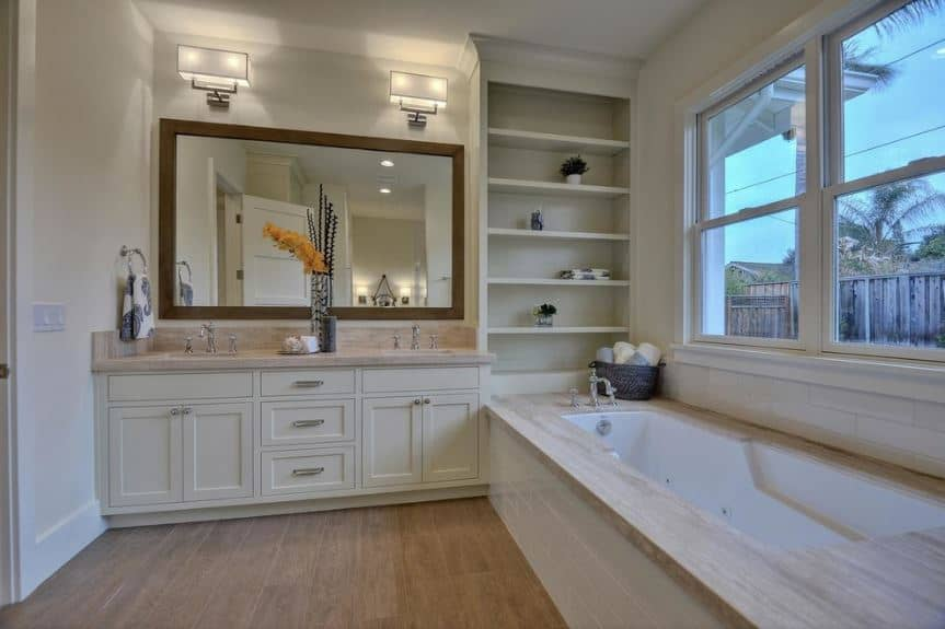 The bathtub that is housed with beige marble and white tiles are beside a tinted window. Adjacent to this is a charming tall shelf attached to the white wooden vanity topped with a wood-framed mirror and modern wall lamps.