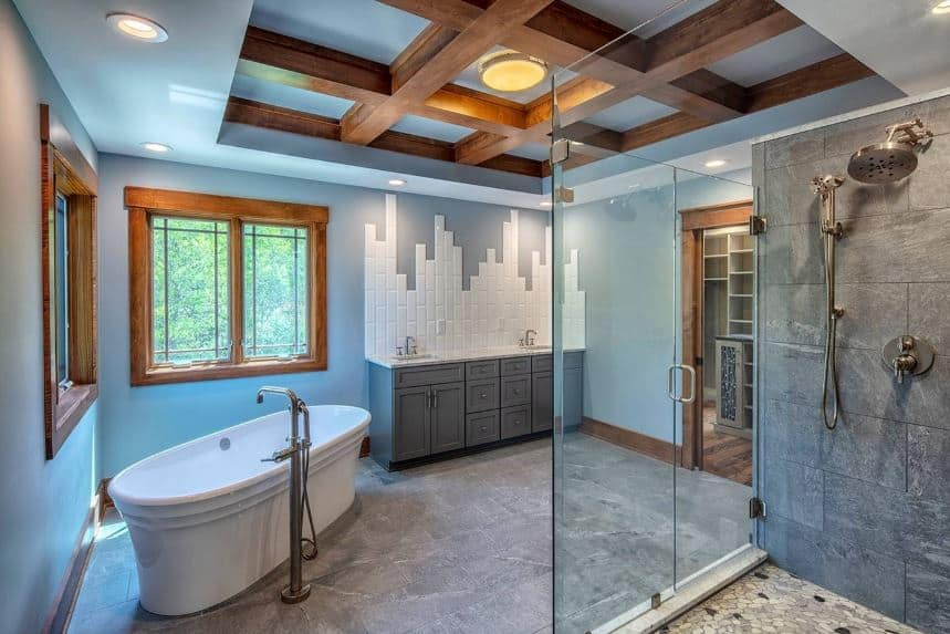 The amazing craftsmanship of this bathroom can be seen on the sleek light blue tray ceiling with a middle tray dominated by wooden exposed beams. This aesthetic is matched with the wood-framed windows on the light blue walls complemented by a gray vanity.