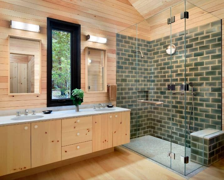 The cathedral ceiling, walls and flooring as well as the floating wooden vanity all share a bare wooden hue that serves as a charming background for the glass-enclosed shower area that has a light green brick wall finish on its walls.