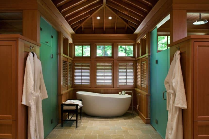 The freestanding white bathtub is placed in an alcove of wooden shuttered windows that blend with the wooden finish of the walls and cathedral ceiling with exposed wooden beams that showcase superb craftsmanship.
