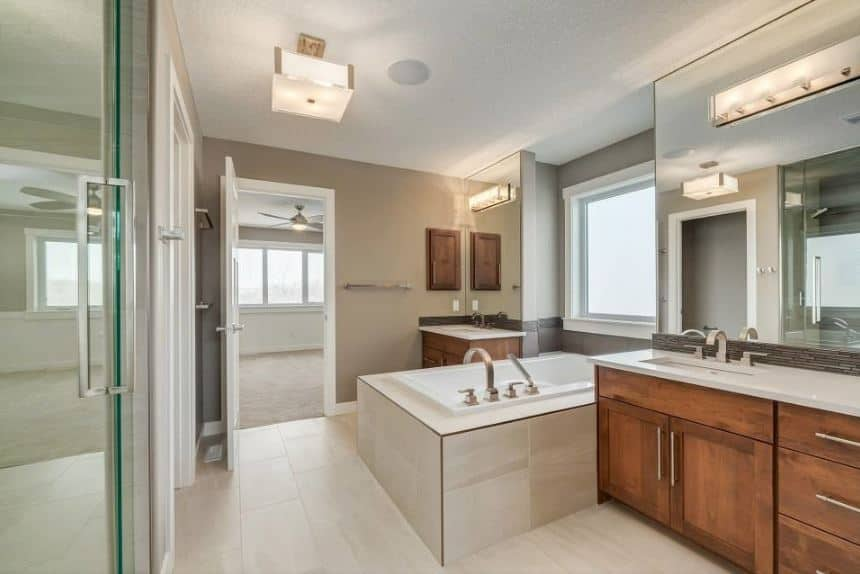 The white flooring tiles are contrasted by the two wooden vanities with white countertops and large wall-mounted mirrors that has modern lamps. These two vanities are flanking a white bathtub inlaid with the same tiles as the flooring.
