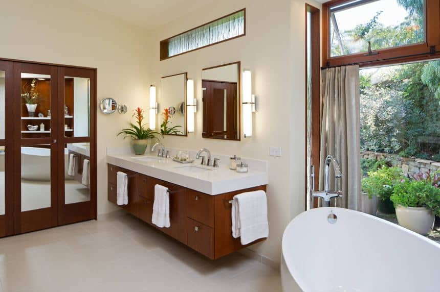 This craftsman-style bathroom features mirrored wooden folding closet doors adjacent to the wooden floating vanity that stands out against the white walls warmed by the yellow lights of the modern wall lamps beside the mirrors.