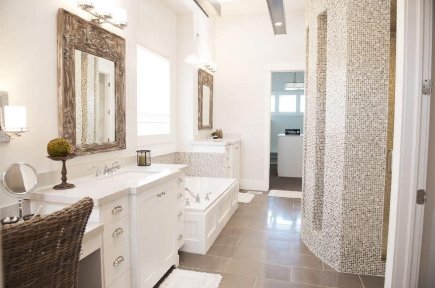 The gray flooring tiles of this bright bathroom is complemented by the complex patterned finish of the shower room and bathtub backsplash. The white walls and white vanities flanking the bathtub are complemented by the elegant wood frames of the mirrors.