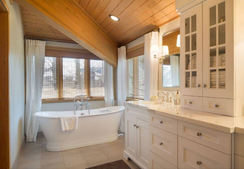 The wooden shiplap ceiling is dominated by a large wooden beam above the white freestanding bathtub placed in an alcove of wood-framed windows with shades. The bathtub matches with the stark white cabinets and drawers of the vanity.