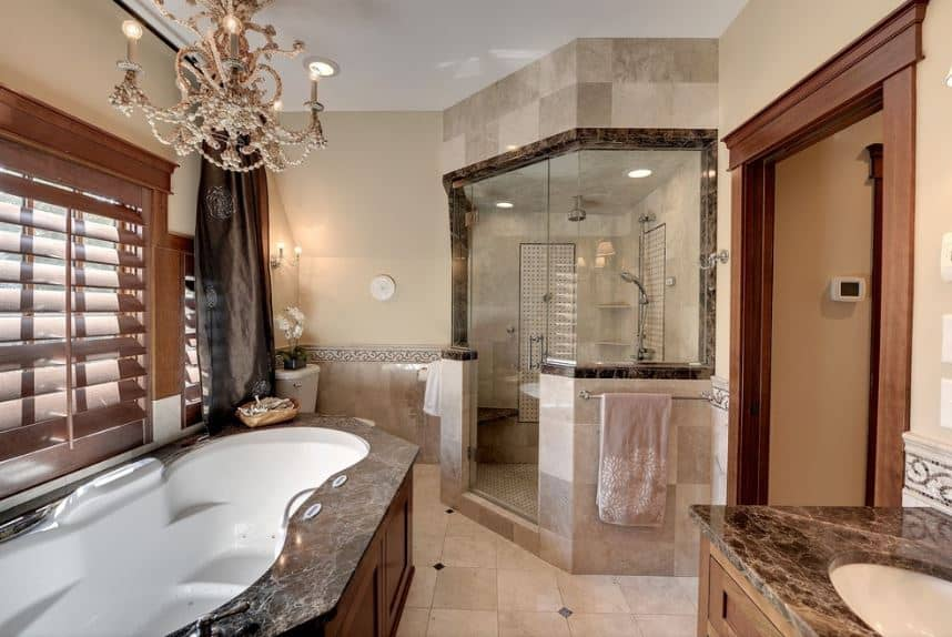 An elegant chandelier hangs over the irregular-shaped bathtub with a black marble countertop and wooden side that matches the wooden shutters and frame of the windows above the tub as well as the vanity with the same wood and black marble combination.