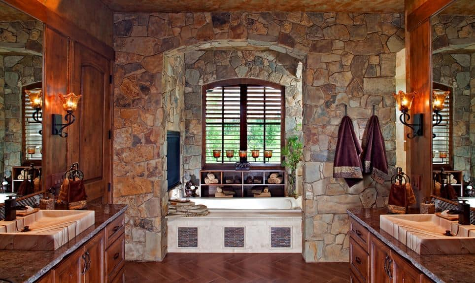 The white bathtub is inside a alcove of stone walls and windows at the far end of the craftsman-style bathroom with two elegant wooden vanities on either sides paired with beige marble sinks and dark countertops.