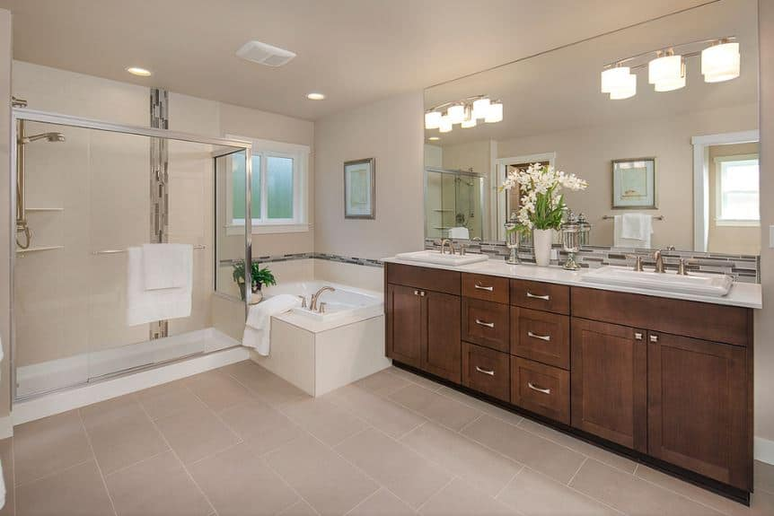 The simplicity of this bathroom is augmented by a dark wooden vanity that has a clean and elegant finish topped with a large wall-mounted mirror accented with wall lamps illuminating the beige walls, ceiling and flooring.