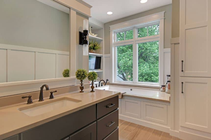 This charming and homey craftsman-style bathroom showcases the woodworks of the bathtub housing that extends to a cabinet on one side and a shelving on the other. This goes well with the modern finish of the gray wooden vanity.