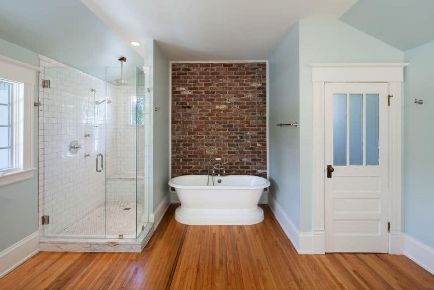This simple bathroom has a glass enclosed shower area and the wooden door flanking the alcove of the white freestanding bathtub that stands out against the hardwood flooring and the red brick wall behind it.