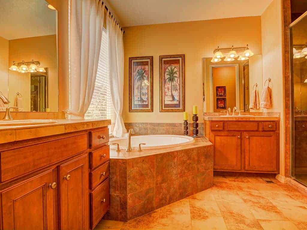 This warm and homey craftsman-style bathroom has a yellow tone to it due to the yellow lights of the wooden vanity wall lamps augmenting the yellow walls. The redwood cabinets and drawers of the two vanities go well with this tone.