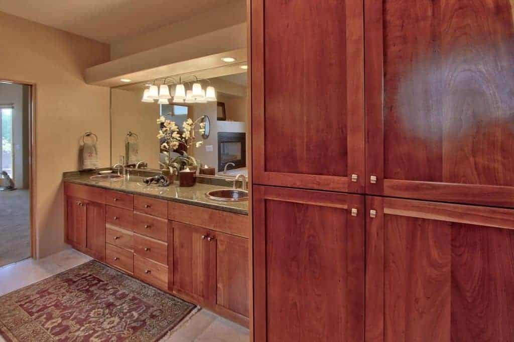 The redwood cabinet and vanity dominates the beige walls of this craftsman-style bathroom that has beige marble flooring topped with a red patterned area rug illuminated by the wall-lamps mounted on the large vanity mirror.