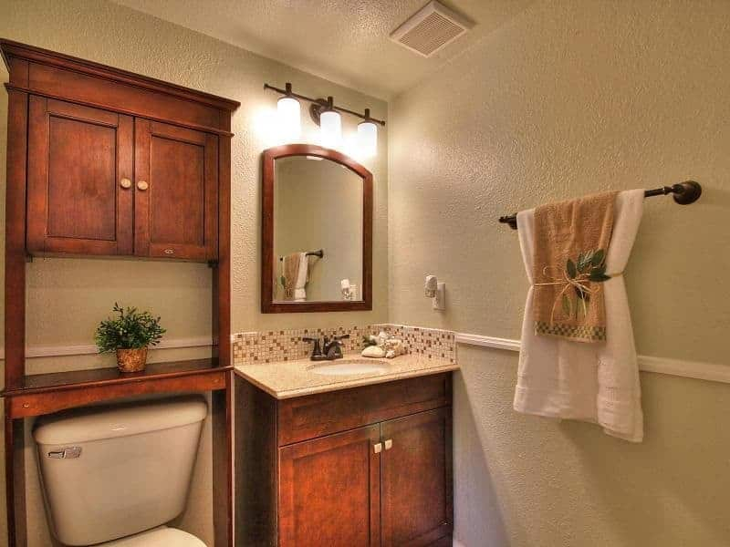 This charming and simple bathroom has textured grainy beige walls that are dominated by the redwood vanity placed in a corner beside the white toilet that is adorned with a redwood structure that has a shelf and cabinets above.
