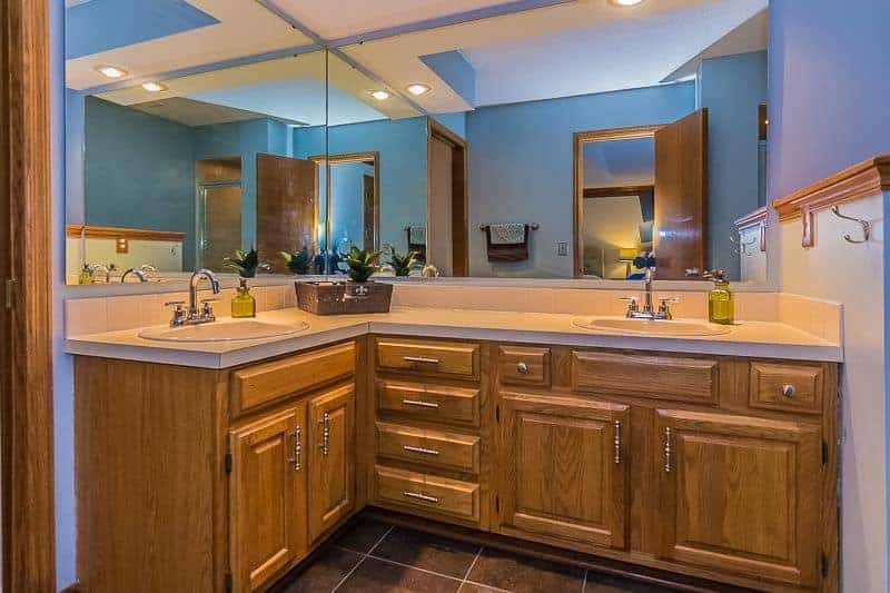 The L-shaped two sink vanity has elegant designs on its wooden cabinets and drawers with silver handles that match the faucets of the sinks topped with mirrors that dominate the walls all the way to the white tray ceiling.