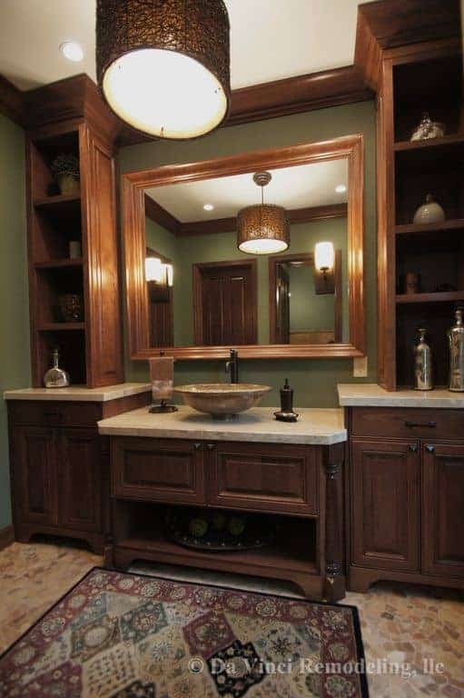 The highlight of this craftsman-style bathroom is the amazing and elegant wooden structure that houses the wooden vanity in between two cabinets with shelves on top that in turn flanks the wood-framed mirror reflecting the pendant light.
