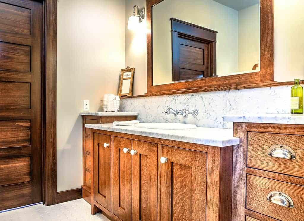 The cabinets and drawers of the wooden vanity have an elegant finish and design that is matched with the wooden frame of the vanity mirror with a wooden shelf below it above the white marble backsplash housing the faucet and its valves.