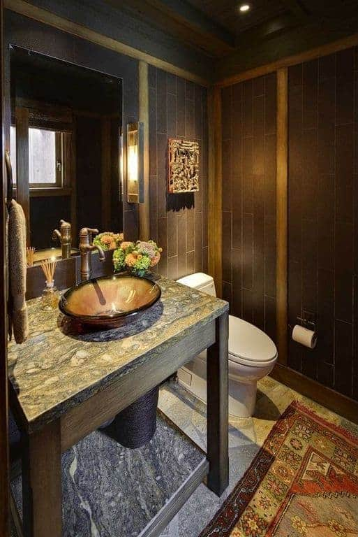 The amazing craftsmanship of this bathroom can be seen on the wooden table supporting the rustic bowl sink and faucet. This craftsmanship is also seen on the wooden ceiling and the wooden finish of the walls that makes the toilet stand out.