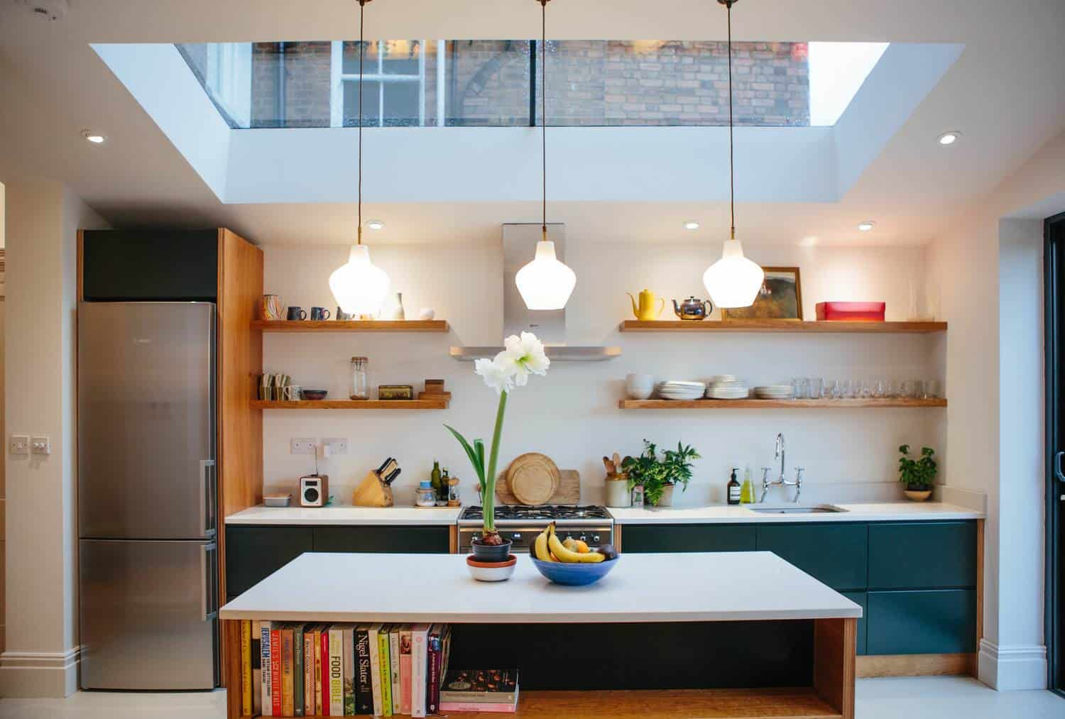 Modern kitchen with a skylight, reclaimed pendant lights over a birch ply kitchen table and cherry veneered birch plywood end panels with green handleless drawer fronts.