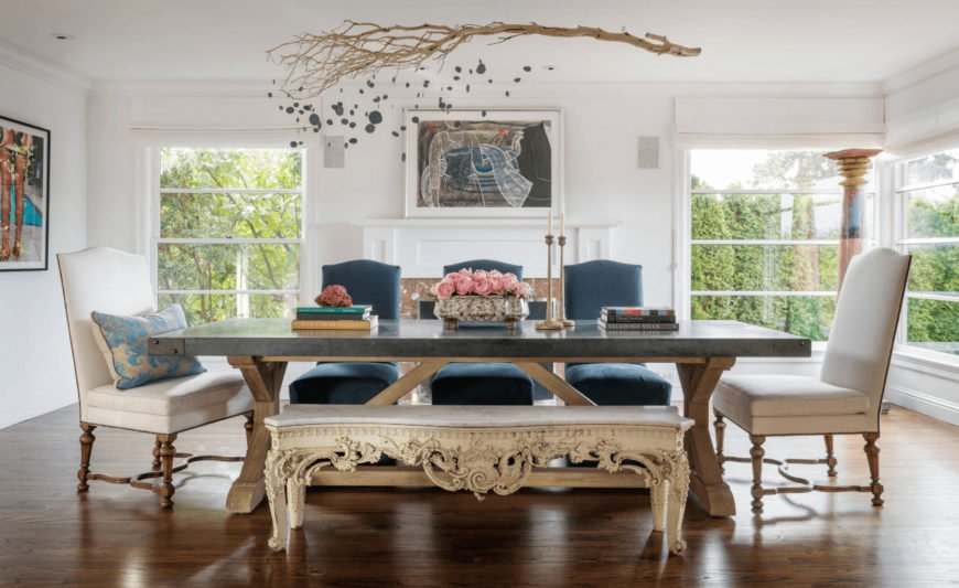 Gorgeous dining room decorated with framed wall arts and a lovely driftwood art piece that hung over the wooden dining table accompanied by an ornate bench and blue and white upholstered chairs.