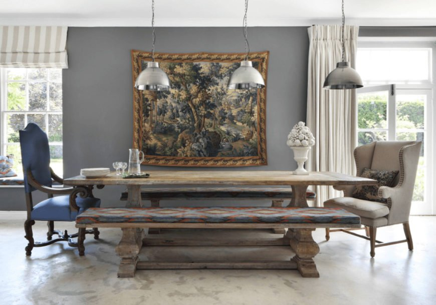 Farmhouse dining room designed with a gorgeous tapestry mounted on the gray wall. It has chrome pendant lights and a rustic dining table surrounded by cushioned benches and mismatched chairs.