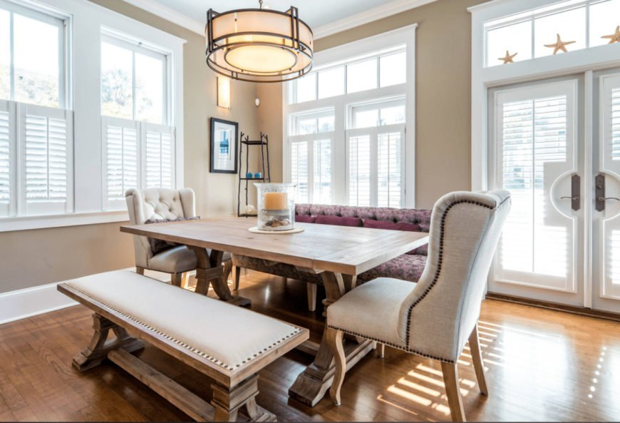 Beach style dining room features mismatched chairs and a wooden dining table lighted by a drum pendant. It is surrounded with a French door and glazed windows covered in white shutters.