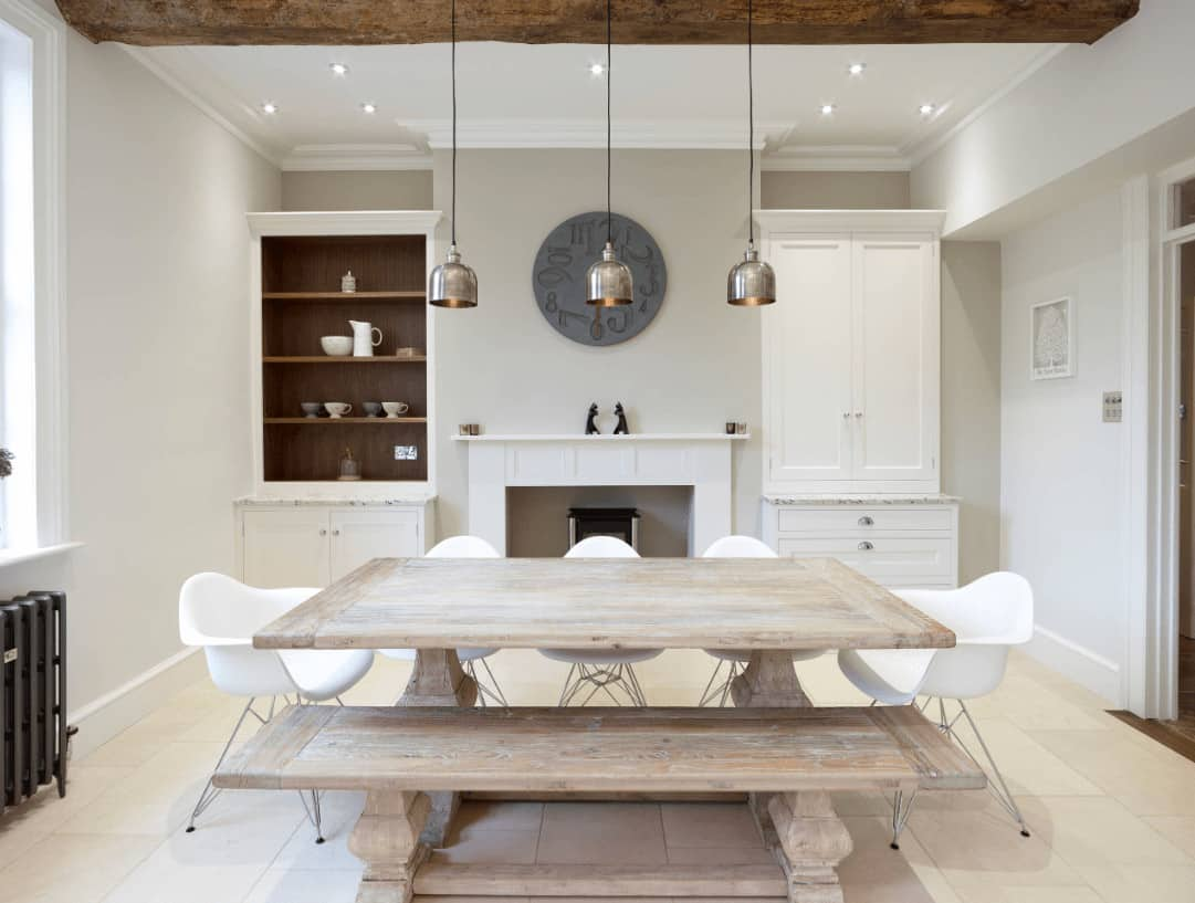Chrome dome pendants hang over the natural wood dining table surrounded with matching bench and white modern chairs in this dining room offering a fireplace flanked by storage cabinets.