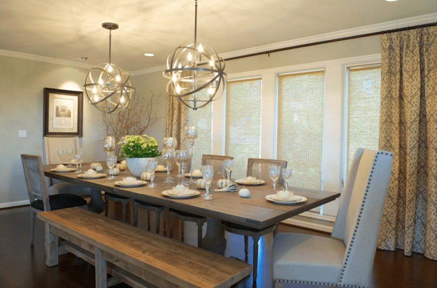 This dining room offers mismatched chairs and a trestle dining table lighted by a pair of spherical chandeliers. It has smooth flooring and glass paneled windows covered with translucent roman shades and patterned drapes.
