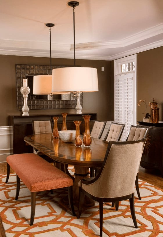 A pair of drum pendants hang over the oval dining table in this contemporary dining room with a cushioned bench and beige tufted chairs that sit on textured area rug designed with an eye-catching pattern.