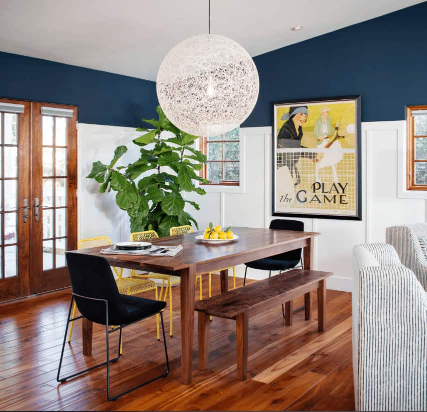 Fresh dining room decorated with a woven chandelier and black framed wall art mounted on the blue wall that's dominated by white wainscoting. It has black upholstered and yellow perforated chairs along with a wooden bench that complements the dining table and hardwood flooring.