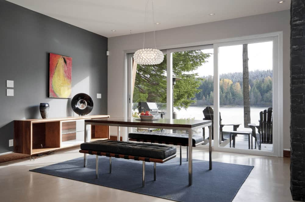 This dining room boasts wooden buffet table and classy dining set lighted by a crystal pendant. It has gray walls and glass sliders that open to the patio with a breathtaking lake view.