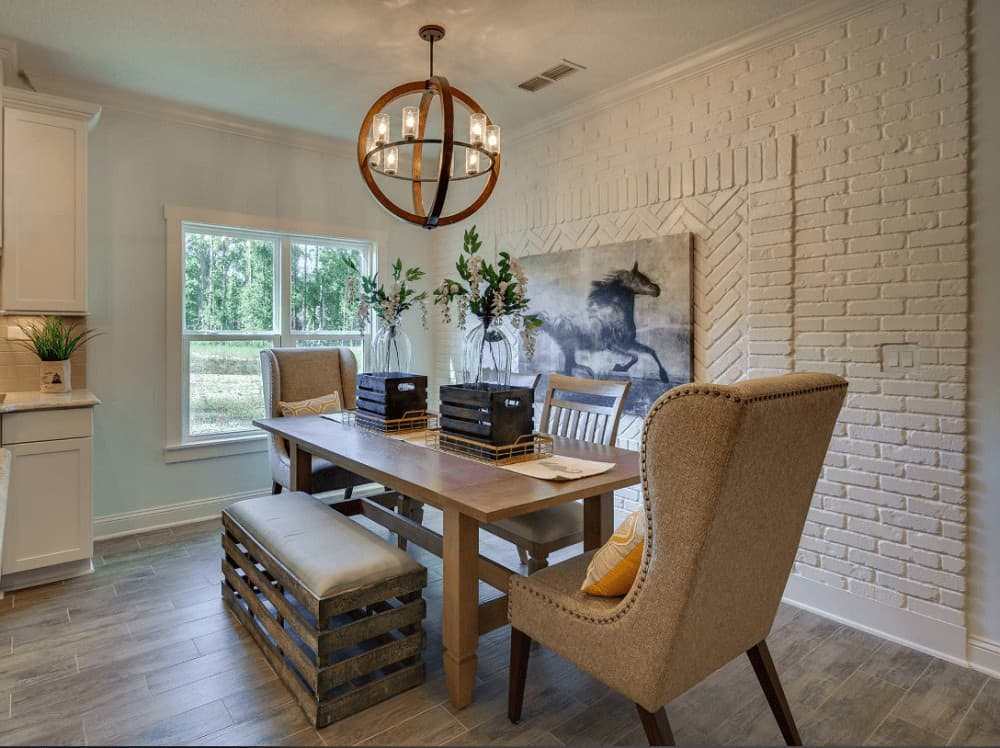 Cozy dining area with wood plank flooring and textured accent wall arranged in brick and herringbone patterns. It has an interesting dining set composed of various styled seats lighted by a spherical chandelier.