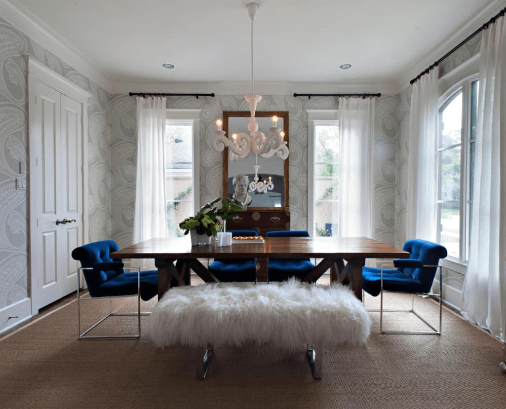 Transitional dining room accented with blue tufted chairs that sit at a wooden dining table illuminated by a unique white pendant. It has a faux fur bench and a drawer chest topped with a rustic mirror.