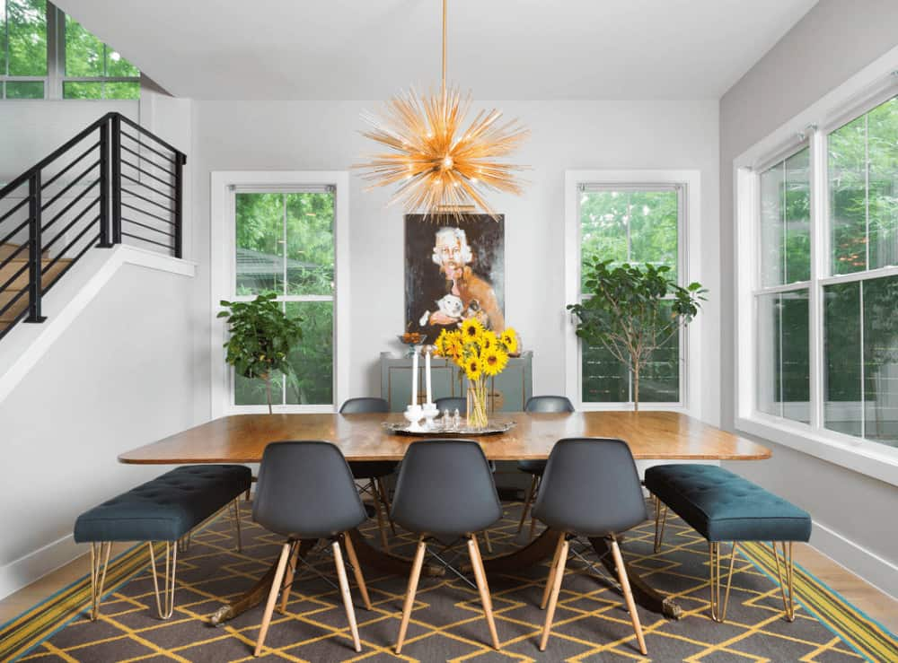 This dining room showcases a sputnik chandelier and a striking diamond pattern rug that lays on the hardwood flooring. It includes a wooden dining table paired with tufted benches and gray modern chairs.