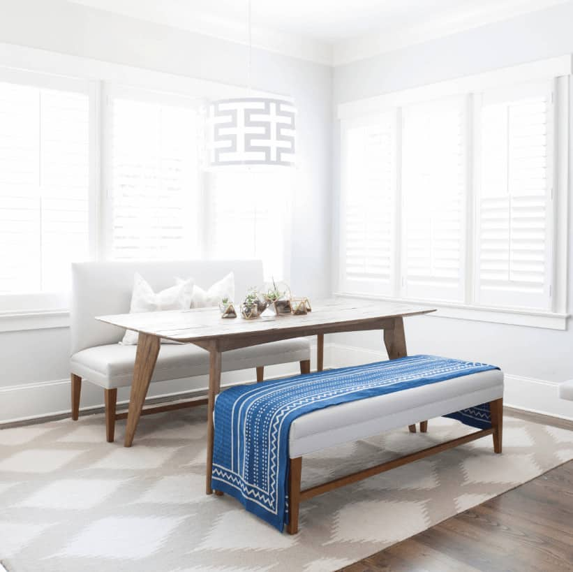 Bright dining room illuminated by a modern drum pendant along with natural light from the louvered windows. It has a natural wood dining table accompanied by a white sofa and bench that's accented with a blue blanket.