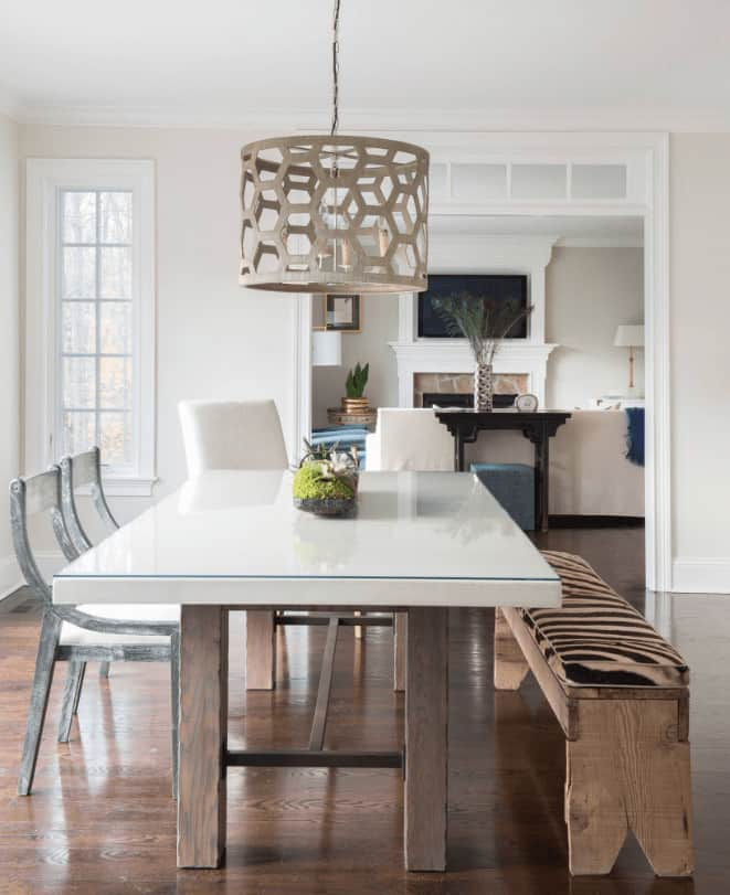 A stylish drum pendant hangs over the white dining table with cushioned chairs and custom bench in this dining area with white framed window and hardwood flooring.