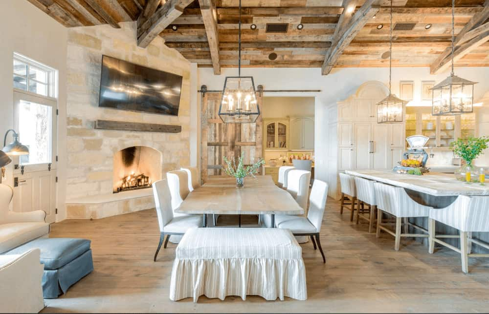 An open dining area with a corner fireplace and a caged pendant light the hung from the wood beam ceiling. It includes white wingback chairs and a skirted bench surrounding a stump dining table accented with a plant centerpiece.