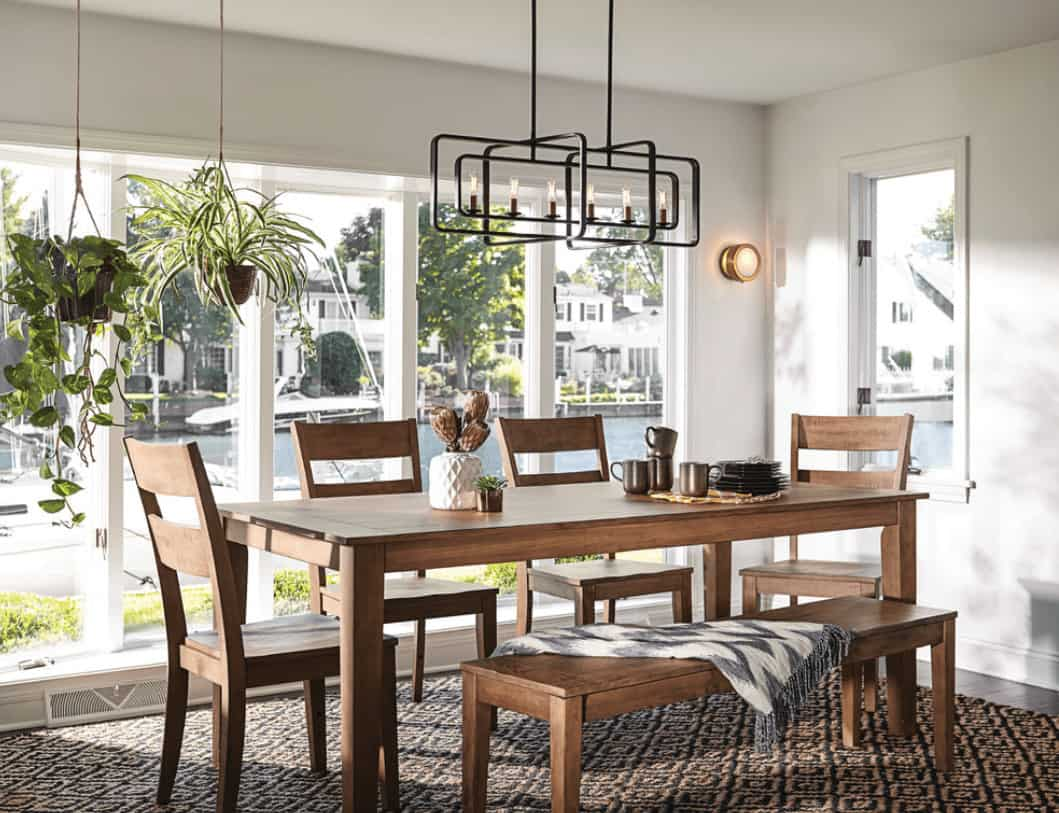 Tropical dining room features an industrial pendant light and a wooden dining set by the glass paneled windows with ample natural light.