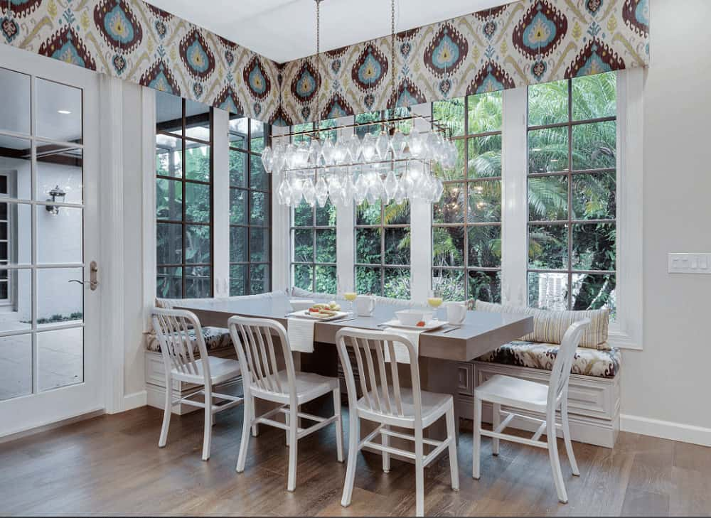 Patterned valances add a charming accent in this transitional dining room with glass chandelier and a sleek dining table surrounded by white chairs and a built-in bench.