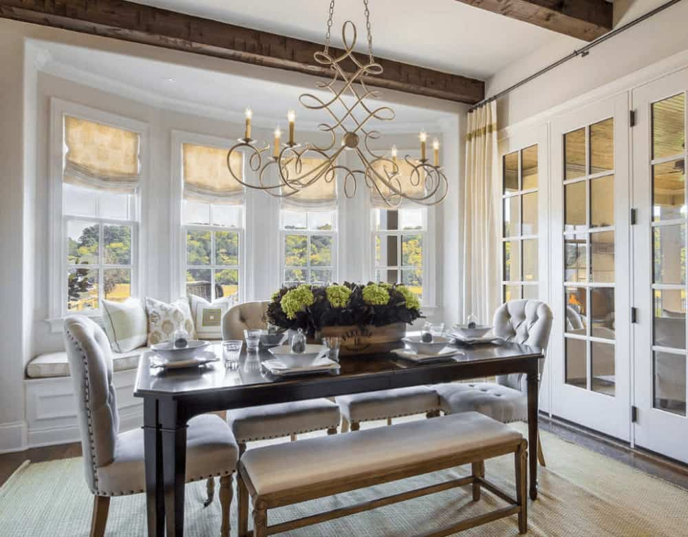 The sophisticated dining room boasts a window seat nook and a classy dining set illuminated by an ornate chandelier that hung from the wood beam ceiling.