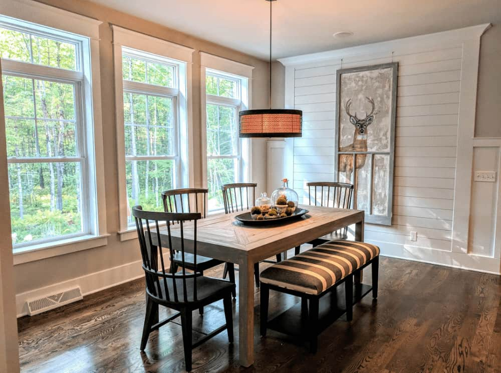 This dining room offers a stylish drum pendant and a stag decor mounted on the shiplap accent wall. It has a natural wood dining table paired with black chairs and a striking striped bench.