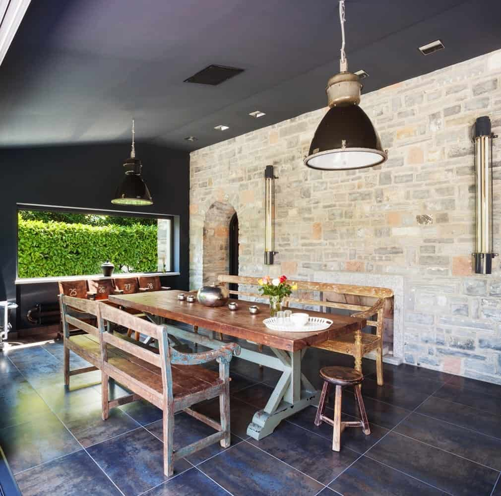A stone brick wall adds a striking texture in this black dining room showcasing a distressed wood dining set and a panoramic window framing the green hedge plants.