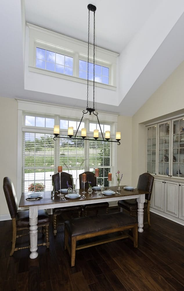 High ceiling dining room with white display cabinet and a wooden dining table paired with black leather chairs and bench. It is lighted by a linear pendant along with natural light from the glazed windows.