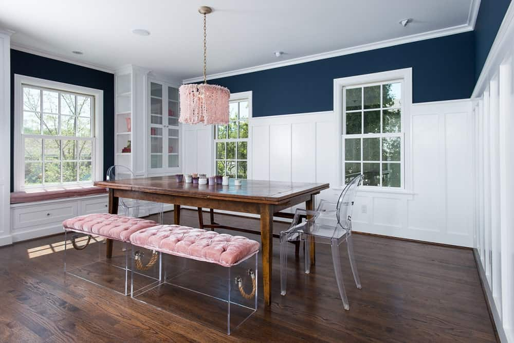 Dining room with blue upper walls, beadboards, lattice windows, and rectangular wooden dining table with a bench seatings and a pair of transparent chairs on hardwood flooring.