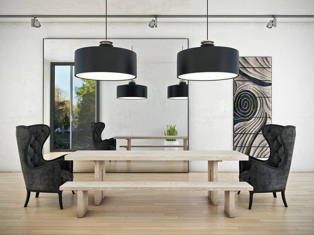 This dining room boasts a large mirror and an eye-catching art piece mounted on the concrete wall. It has a natural wood dining table accompanied by a matching bench and black wingback side chairs.