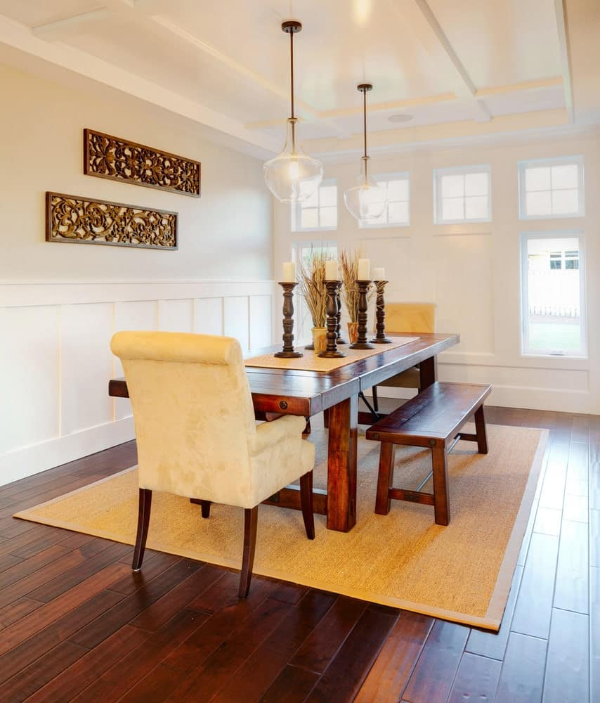 This dining room is decorated with glass pendants and a pair of carved wood art pieces mounted on the white wall. It has a jute rug and a dark wood dining table paired with matching benches and beige velvet chairs.