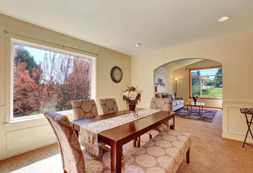 Gorgeous dining room with carpet flooring and a picture window overlooking the outdoor scenery. It includes a smooth dining table lined with a tasseled runner that complements the patterned chairs and bench.